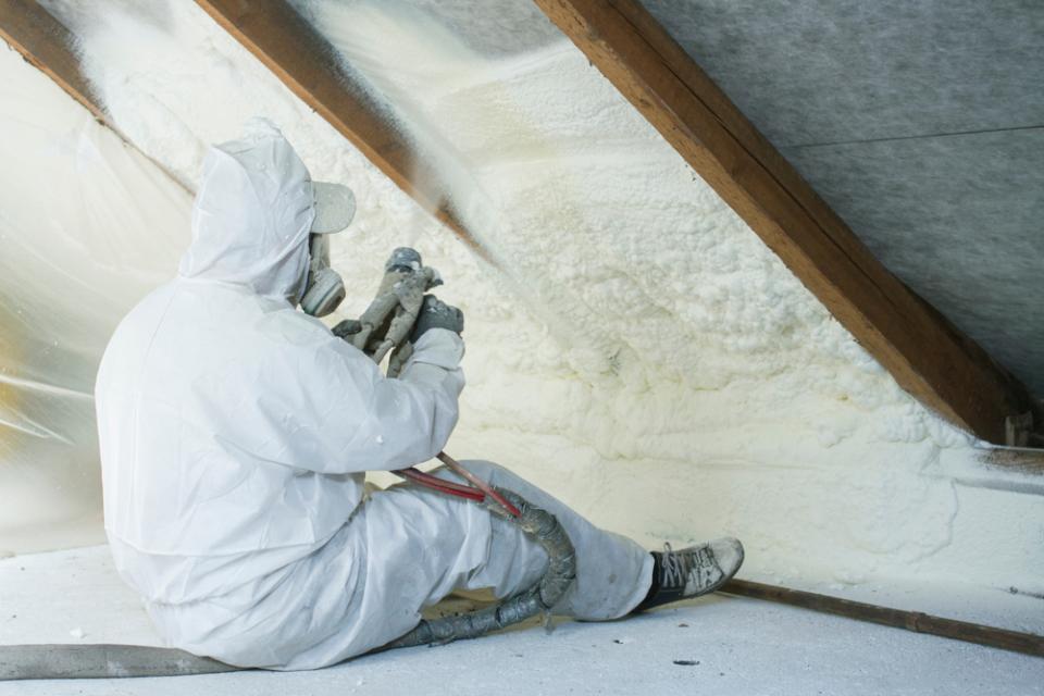 Worker applying spray foam insulation to interior of roof