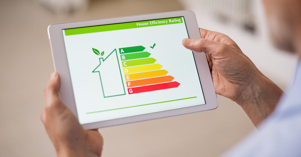 Man Holding Tablet with Readings of an Energy Efficient House on the Screen