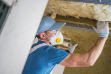 A professional worker installing insulation